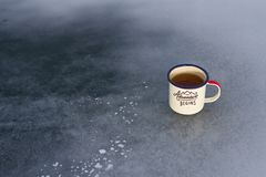 Camping enameled metal traveler`s mug with herbal tea on the textured ice of Lake Baikal in winter. Camping enameled metal traveler`s mug with herbal tea on the Royalty Free Stock Image