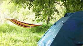 Camping equipment: touristic Tent and Hammock between the trees Royalty Free Stock Photo