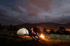 Camping evening couple sitting on boards near campfire Stock Photography