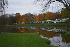 Camping in the Fall. Fall color and Recreational Vehicles reflected in the lake Royalty Free Stock Image