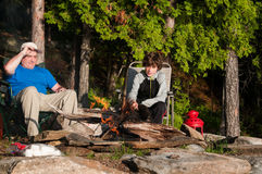Camping father and son. Father and son sitting by a campfire roasting marshmallows Stock Photos