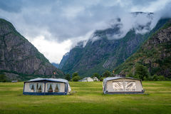 Camping field with camper tents under the rocky mountains of norwegian fjord. Royalty Free Stock Photos