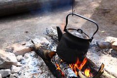Camping fire. Tea-kettle on the camping fire stock photography