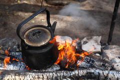 Camping fire. Tea-kettle on the camping fire stock photo