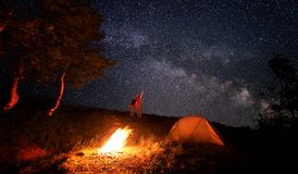 Camping fire and tent under the amazing starry sky with lot of shining stars. Camping fire and orange tent under the amazing starry sky with a lot of shining stock photo