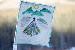 Camping flag showing a simple indian tent with mountains and sun in the back, hand drawn on a white hemp cloth. Blurry background with grass, during Spring stock photos