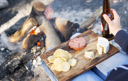 Camping Food. Gourmet camping food on a wooden board, with cheese, salami and crackers with a beer in front of the fire royalty free stock photo