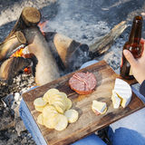 Camping Food. Gourmet camping food on a wooden board, with cheese, salami and crackers with a beer in front of the fire royalty free stock images