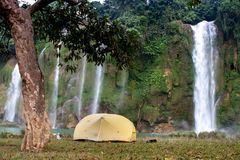 Camping in front of Ban Gioc waterfall, North. Camping in front of Ban Gioc waterfall, North Vietnam. Yellow tent in front of waterfall. Version 2 Royalty Free Stock Image