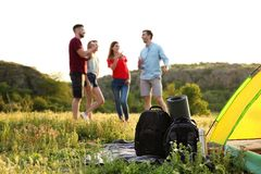 Camping gear and group of people in wilderness. Camping gear and group of young people in wilderness royalty free stock photo