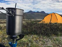 Camping Gear in the Mountains. Yellow tent and boiling kit in the mountains of Ecuadorian highlands. Taken at about 4000 mts above sea level. the volcano at the Royalty Free Stock Photos