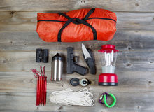 Camping gear and personal protection accessories. Overhead view of hiking gear and personal protection, pistol and knife, placed on rustic wood Stock Photos