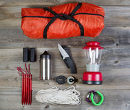 Camping Gear on Rustic Wooden Boards. Overhead view of basic hiking gear placed on weathered wooden boards. Items include tent inside of bag, pegs, compass Stock Photos