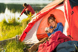 Camping girl in tent drinking from pot Royalty Free Stock Photos