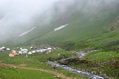 Camping ground beside creek and hills. Green hills and cloudy weather royalty free stock photography