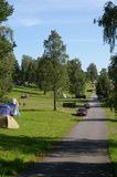 Camping grounds in Oslo. This is the Camping grounds of Bogstad in Oslo. Scene is a straight road on left of image with tents in a clearing beside the road. Cars Royalty Free Stock Photo