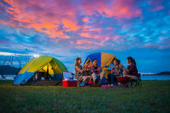 Camping of happy asian young travellers at lake. Asian men and women group, relaxing, sing a song and cooking, at sunset stock photography
