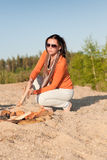 Camping happy woman making campfire on beach Stock Photography