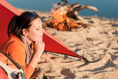 Camping happy woman relax in tent by campfire Stock Image