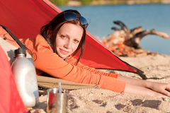 Camping happy woman in tent by campfire Stock Image