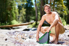 Camping hiker man on trek washing clothes in river. Camping hiker man washing clothes on trek in nature river. Hiking young male adult doing clothing wash chores Royalty Free Stock Photos