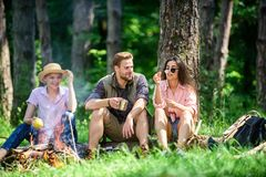 Camping and hiking. Company friends relaxing and having snack picnic nature background. Company hikers relaxing at. Picnic forest background. Halt for snack royalty free stock images