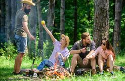 Camping and hiking. Company friends relaxing and having snack picnic nature background. Great weekend in nature. Company. Hikers relaxing at picnic forest royalty free stock image