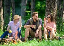 Camping and hiking. Halt for snack during hiking. Company friends relaxing and having snack picnic nature background. Company hikers relaxing at picnic forest royalty free stock image