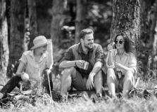 Camping and hiking. Halt for snack during hiking. Company friends relaxing and having snack picnic nature background. Company hikers relaxing at picnic forest stock photography