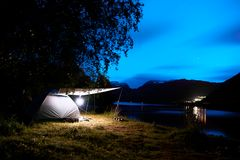 Camping with a illuminated tent at the beach and fjord in the mountains of Norway during night with a cloudy blue sky and stars. The tent is standing on the Royalty Free Stock Images