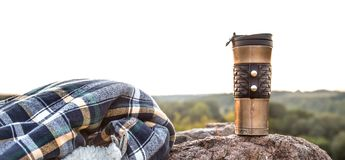 Camping items on the background of nature. Camping items, thermos with jacket on a stone on the background of nature, the concept of travel and recreation stock image