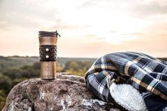 Camping items on the background of nature. Camping items, thermos with jacket on a stone on the background of nature, the concept of travel and recreation stock photos