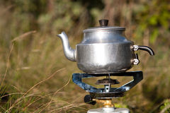 Camping kettle. A camping kettle on a gas stove outdoors Royalty Free Stock Images