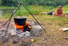 Camping - kettle and lying tourist stock photography