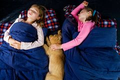 Camping kids. Two young girls and a Golden Retriever Puppy sleeping in warm sleeping bags in a tent while camping stock image