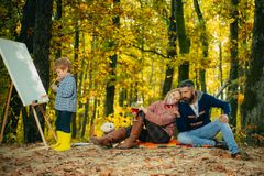 Camping with kids. Little artist painting picture. Autumn garden party Father, mather and son. We like autumn time stock image