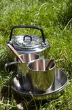 Camping kitchenware. Kettle and mugs on the grass Stock Image