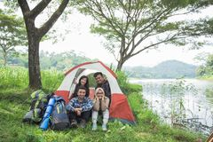Camping by a lake with friends. Happy friends together camping by a lake sitting inside a tent together Royalty Free Stock Images