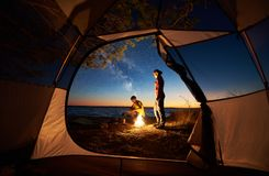 Young couple man and woman having rest at tourist tent and burning campfire on sea shore near forest royalty free stock image
