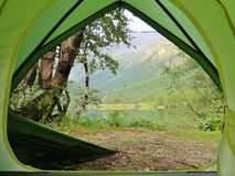 Camping at the lake. Sport lifestyle, healthy living, tents, national park, nature, nature reserve, summer, holidays, trekking, green grass, green tent, blue stock images