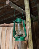 Camping lantern. Green camping lantern hanging in front of a wooden hut stock photos