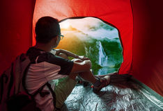 Camping man in camper tent looking to beautiful natural water fa Stock Photo