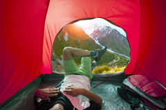 Camping man lying in outdoor camping tent with beautiful natural Royalty Free Stock Images