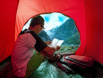 Camping man reading traveling guide book in camp tent against be. Autiful scenic of glacier mountain royalty free stock image