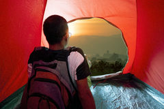 Camping man in tent and sun rising sky Stock Photography