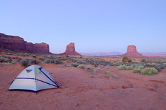 Camping in Monument Valley. Navajo Nation: a small tent in the desert with mesas lit by rising sun in the background Stock Images