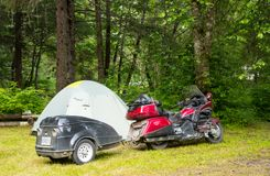 Camping with a motorbike in the wilderness. Bikers with a pitched tent as seen at a campground in alaska Stock Image