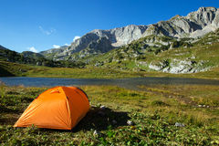 Camping in mountain lake. On green grass stock images
