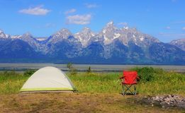 Camping in the mountain wild flowers with the grand tetons mountain range in the back ground. In the spring. With a camp chair setup to view the mountain range stock photography