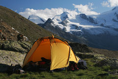 Camping in the mountains. Yellow tent on green meadow with snow peaks in the background Royalty Free Stock Images